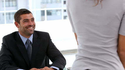 Woman leaving an interview with a businessman