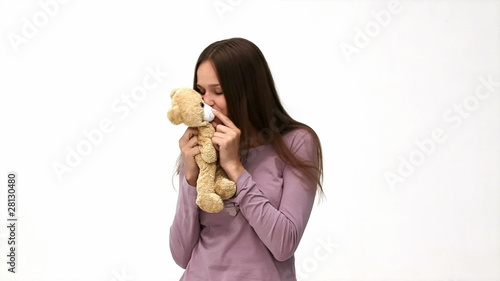 Cute woman kissing a teddy bear against a white background