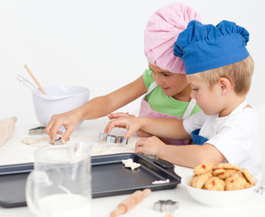 Adorable siblings cooking biscuits together in the kitchen