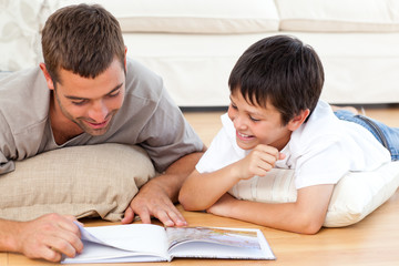 Happy father and son reading a book together on the floor