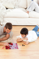 Father and son playing checkers together lying on the floor