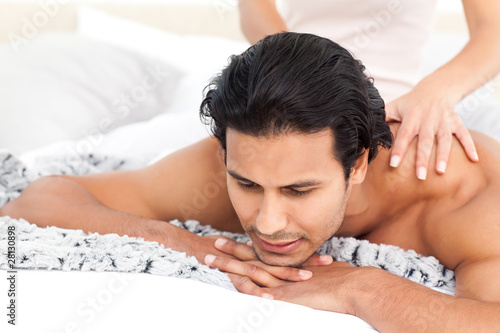 Passionate woman doing a massage to her boyfriend lying on their