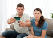 Worried couple cutting their credit card on the sofa