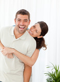 Cheerful woman hugging her husband standing in the living room