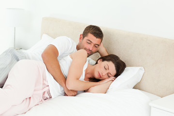 Passionate man looking at his girlfriend sleeping peacefully