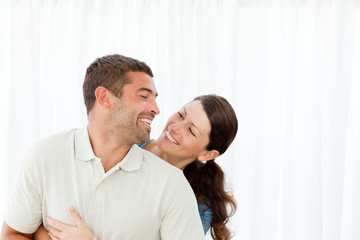 Lovely couple laughing together in the living room