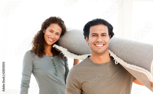 Cute couple carrying a carpet standing in the living room