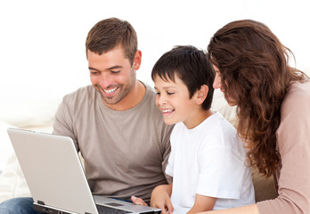 Cute family working on their laptop together sitting on the sofa