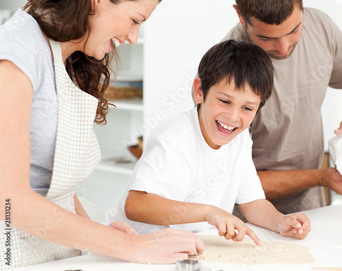 Cheerful family having fun while preparing biscuits together