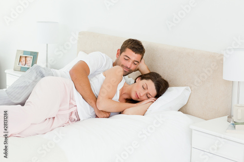 Attentive man looking at his girlfriend sleeping