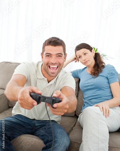 Bored woman looking at her boyfriend playing video game on the s