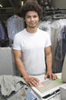 Portrait of young man working in dry cleaners
