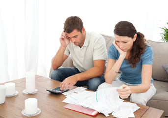 Desperate couple doing their accounts sitting on the sofa