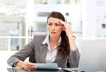 Serious female executive finding ideas while working at her desk