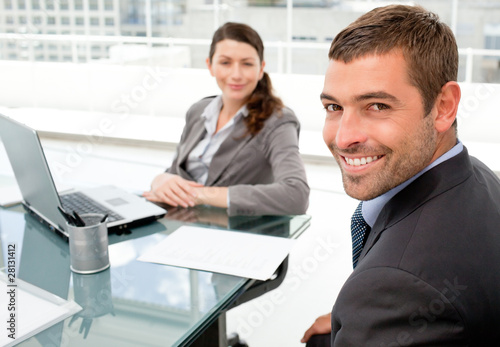 Cheerful business people working on a laptop during a meeting