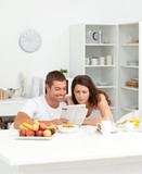 Happy couple reading the newspaper in the kitchen