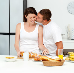 Passionate man kissing his girlfriend while cutting bread for br