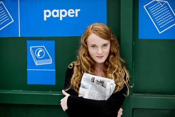 A teenage girl standing next to a recycling container for paper