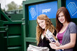 Two teenage girls standing next to a recycling container