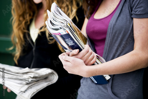 Two teenage girls holding magazines and newspapers