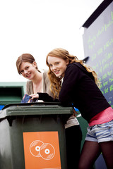 Two teenage girls recycling cds