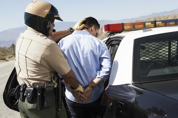 Police officer guiding apprehended man into police car