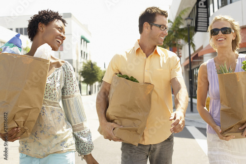Friends walking with groceries in hand, portrait