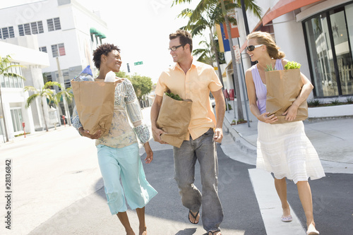 Three mid-adult friends on street holding groceries