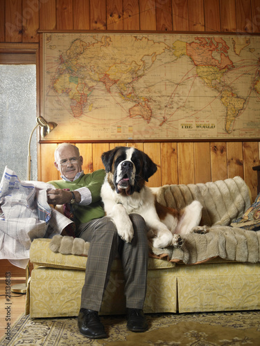 Senior man sharing sofa with large St Bernard dog
