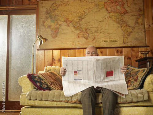 Senior man sitting on sofa, reading newspaper