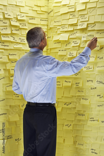 Middle-aged man standing in front of wall covered in sticky notes, reading