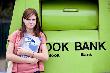 A teenage girl standing next to a recycling container for books