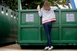 A teenage girl recycling a drink can, rear view