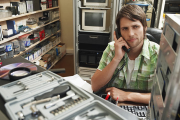 Man using phone, surrounded by computer equipment.