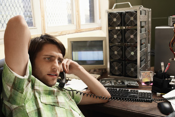 Man using phone, with computer equipment in background.