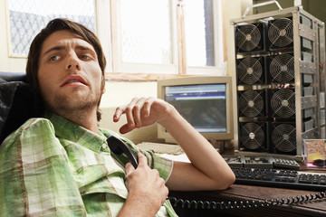 Man sitting at desk with computer equipment, holding phone.