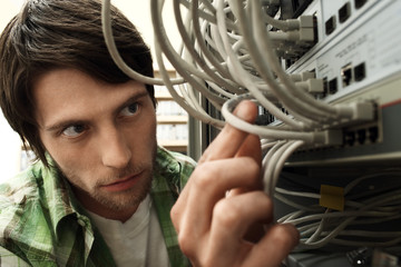 Man working on network switch, close-up.