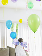 Young girl 7-9 climbing on sofa, wearing fairy wings, back view