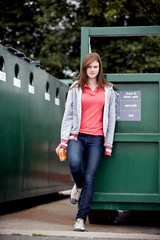 A teenage girl standing next to a recycling container