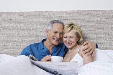 Middle aged couple in bed, woman reading newspaper, man drinking coffee
