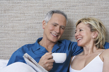 Middle-aged couple in bed, smiling