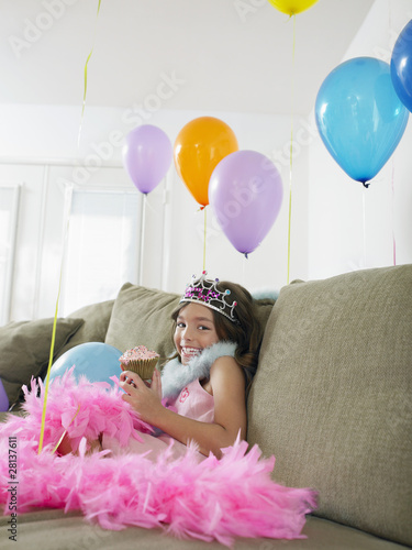 Young girl 7-9 sitting on sofa with balloons, eating cupcake