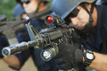 Swat officer aiming guns