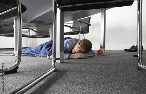 Man sleeping on floor under desk in boardroom