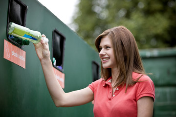 A teenage girl recycling a plastic bottle, smiling