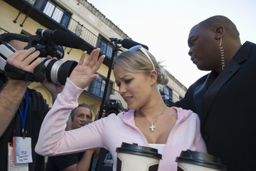 Female celebrity with bodyguard and paparazzi