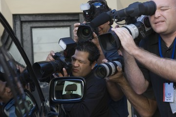 Paparazzi photographers at car window