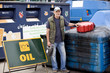 A senior man standing next to a recycling container for oil