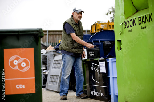 A senior man recycling a car battery