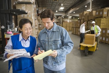 Woman and man talking in distribution warehouse